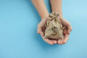 Women hold a money bag on light blue background, Saving money for future investment concept.